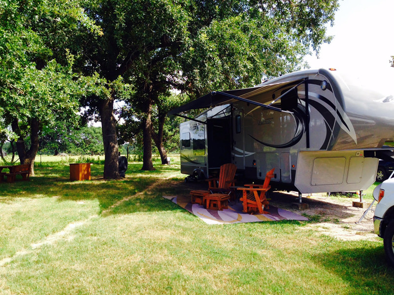 RV With Tablle And Lounge Chairs At Our RV Park In San Antonio